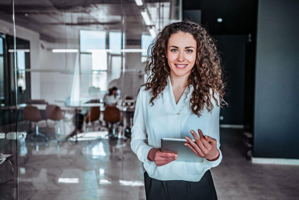 A women standing in a modern office, holding an iPad.